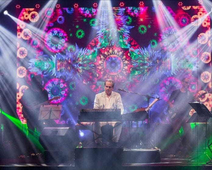 musician with keyboard amd colorful background with lights