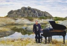 Brazilian pianist Ricardo Bacelar standing nest to grand paino in Ceara Brazil