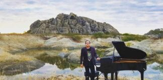 Brazilian pianist Ricardo Bacelar standing nest to grand paino in Ceara Brazil